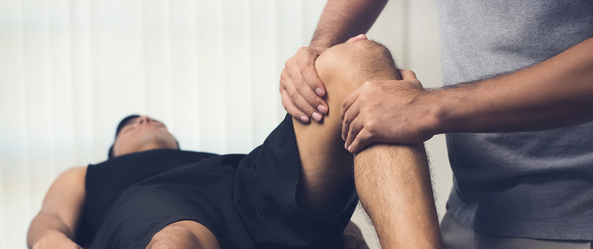 Physical therapist treating patient with knee pain following knee surgery