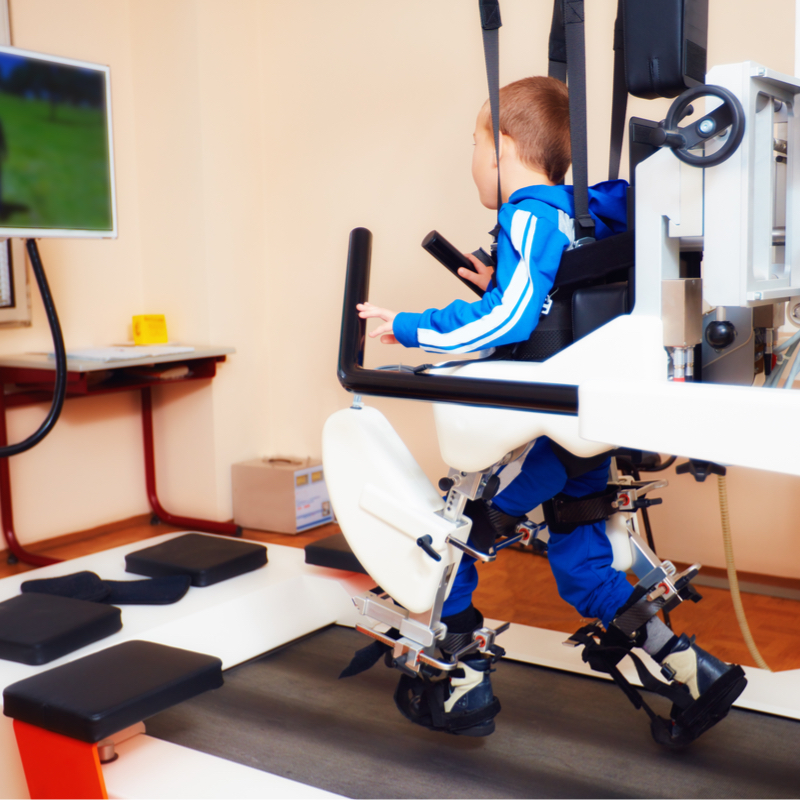 Young boy on gait training machine