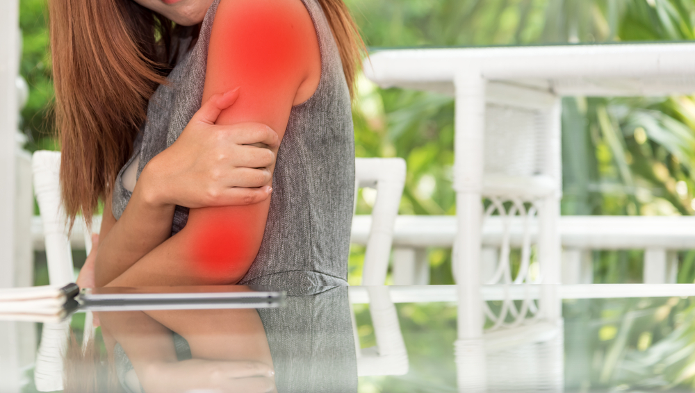 Woman holding arm in pain
