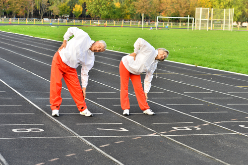 elderly people stretching on track