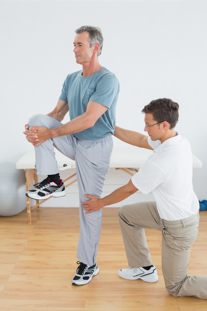 Male physical therapist helping patient with balance