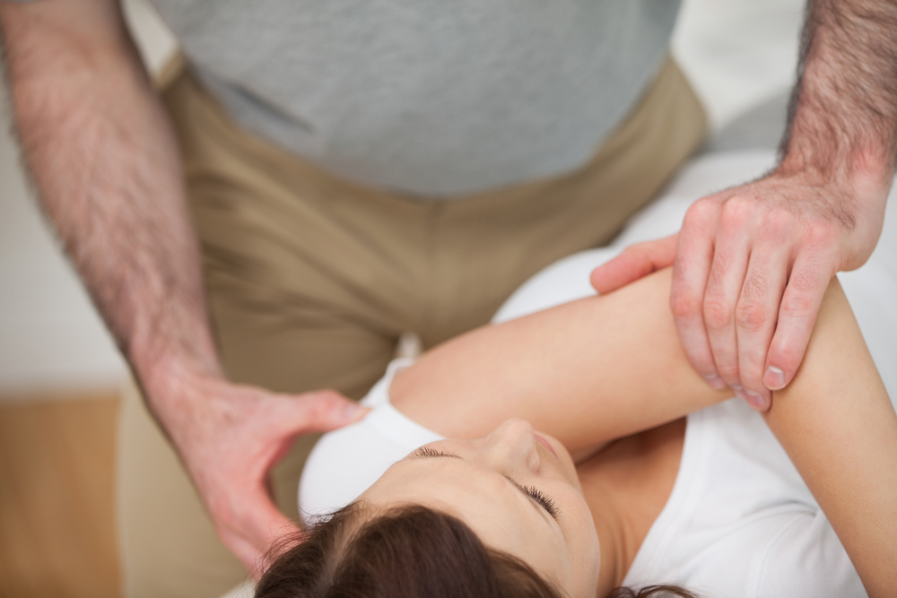Physical therapist providing joint mobilization on patient shoulder