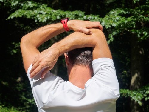 man doing triceps stretch