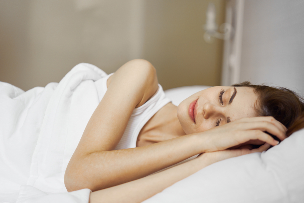 Side view of a woman sleeping in bed with her hands over her face
